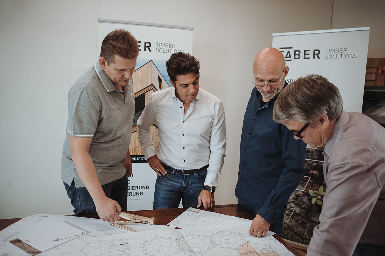 Geschäftsführung und Mitarbeiter begutachten Baupläne